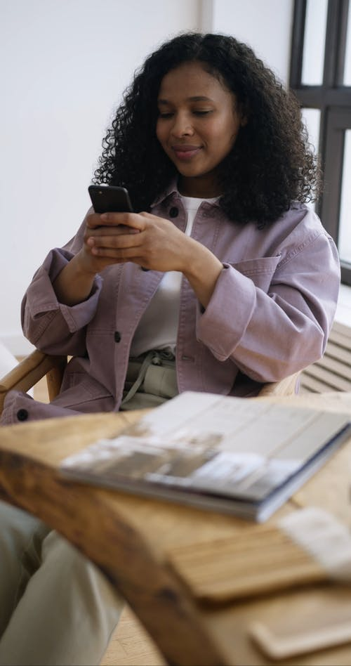 A Woman Smiling while Holding Her Mobile Phone