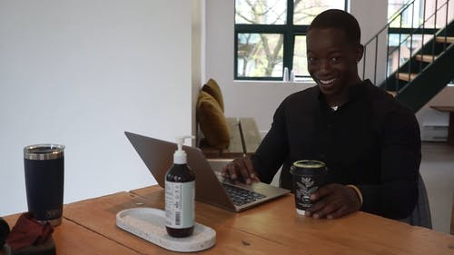 A Happy Man Talking while Using a Laptop
