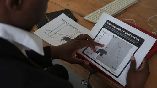 A Man Looking at a Document about the Stock Market