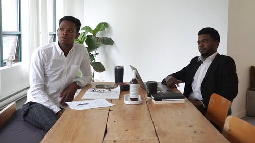 Men in Corporate Attire Sitting at a Table