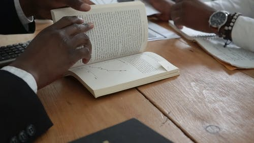 A Person Looking at a Graph in a Book