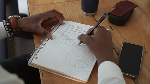 A Person Drawing a Graph in a Notebook
