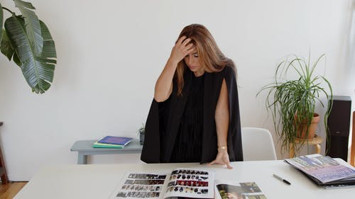 A Woman Standing While Looking at the Magazines