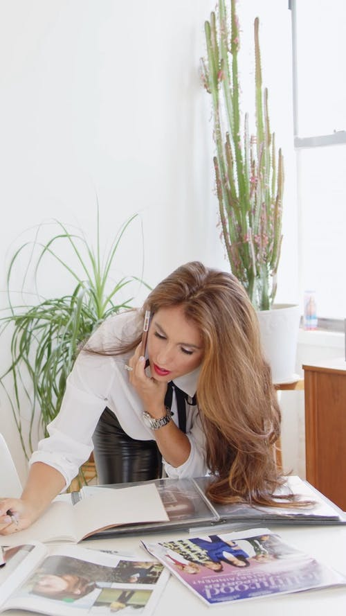 A Woman Writing while Talking on the Phone
