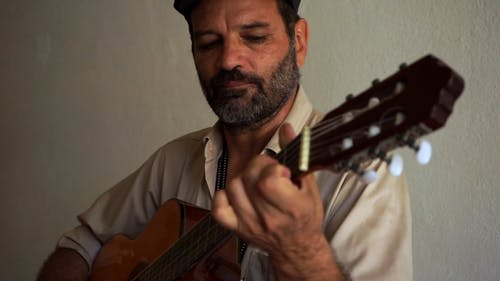 A Bearded Man Playing Guitar