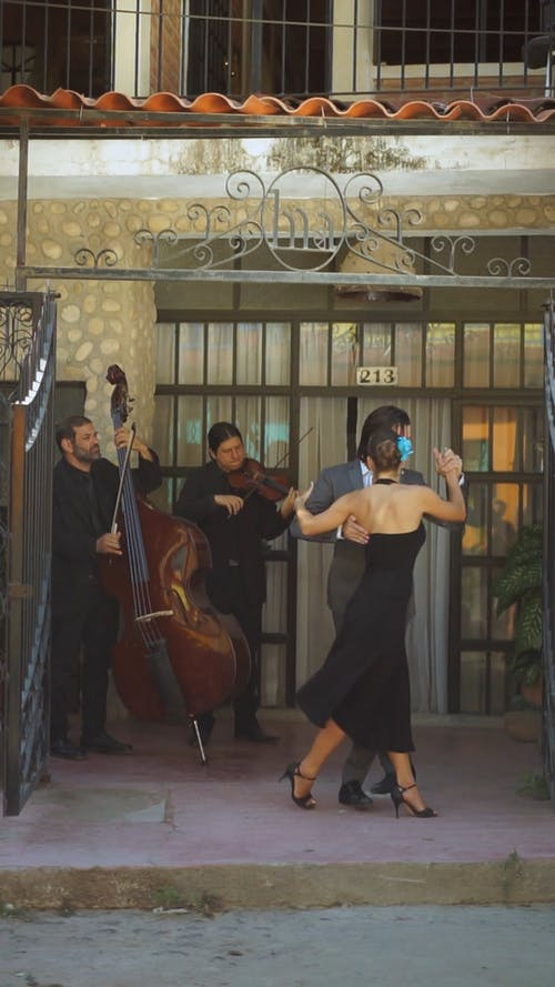 A Man and a Woman Dancing the Tango Outside of a Building