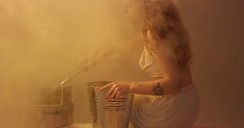 Woman Pouring Hot Water In A Bucket