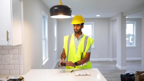 A Man Measuring Height of Ceiling