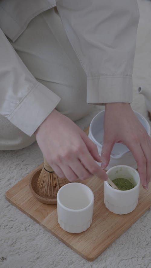 A Woman Putting Matcha Powder on a Ceramic Pot