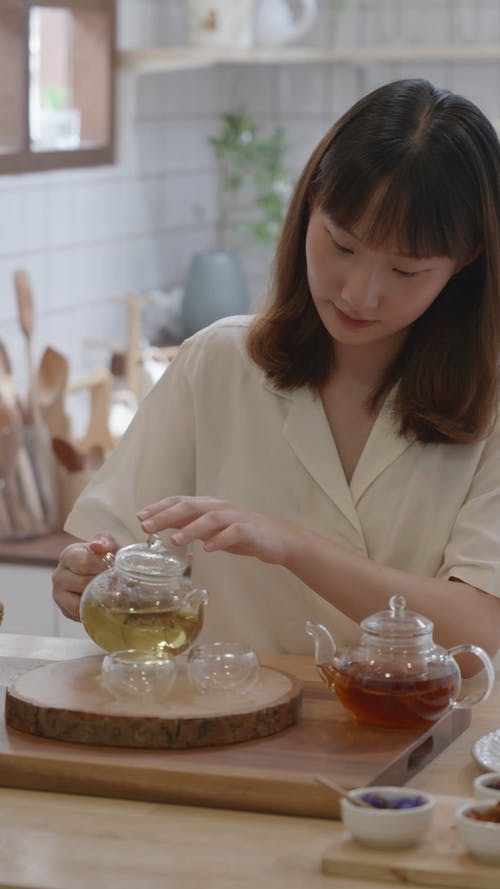 A Woman Pouring Tea on the Teacups