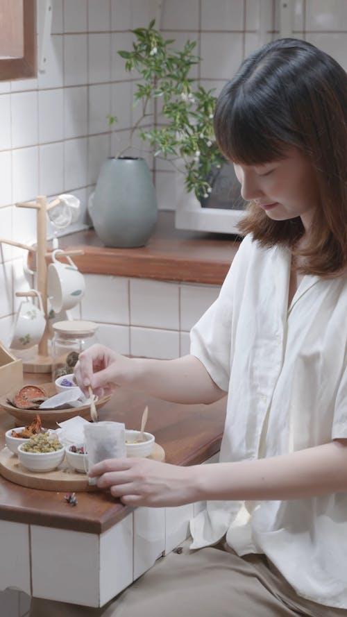 A Woman Putting Tea on a Teabag