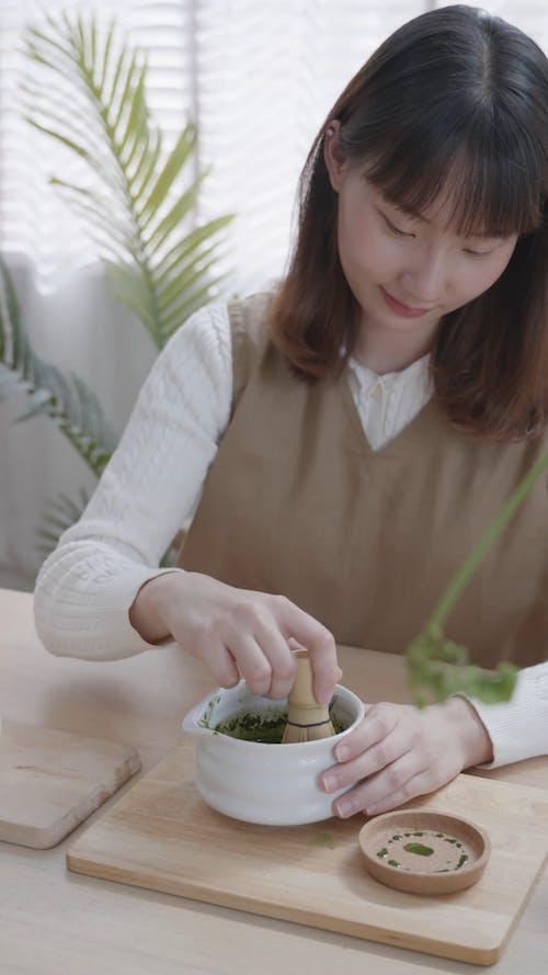 A Woman Stirring LIquid in a Bowl