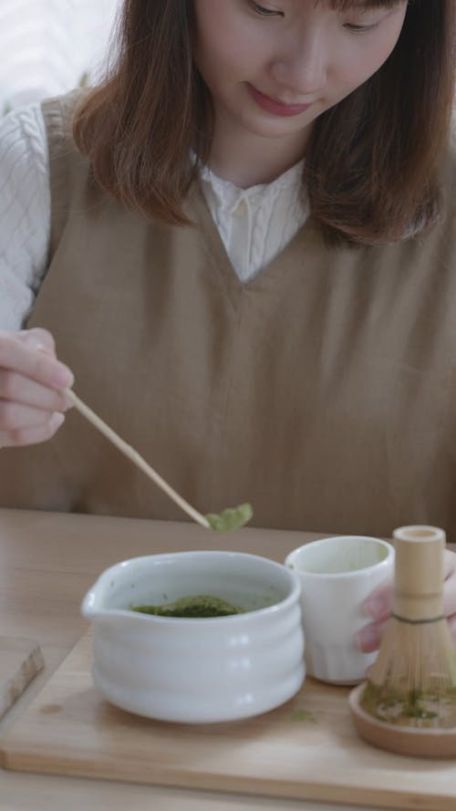 A Woman Scooping Ingredient to a Bowl