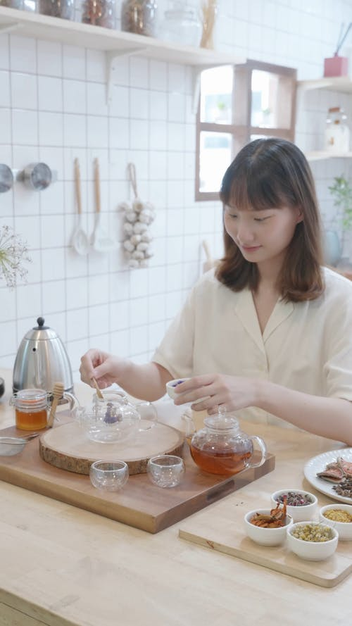 A Woman Putting Dried Flowers on a Glass
