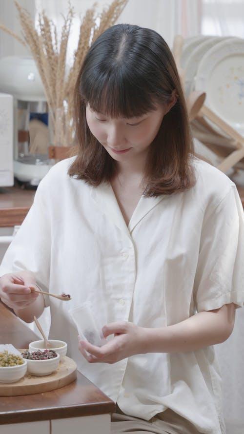 A Woman Putting Dried Flowers on a Tea Bag
