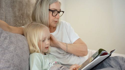 An Elderly Woman and a Girl Reading a Book