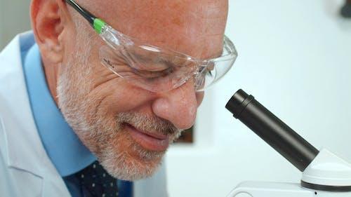 A Scientist Looking Into A Microscopeclo