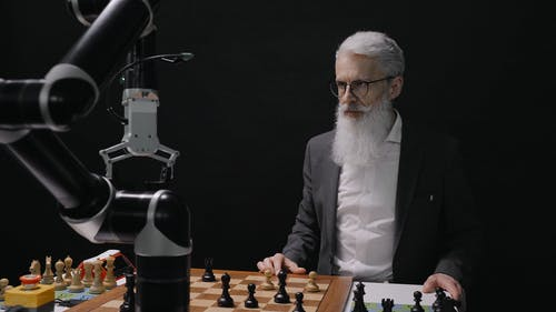 Man Observing A Robot While Playing Chess