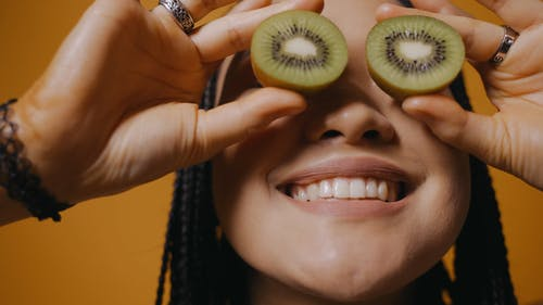 Woman Covering Her Eyes with Sliced Kiwis