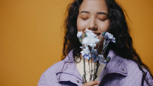 Happy Woman Holding Flowers Near Her Face