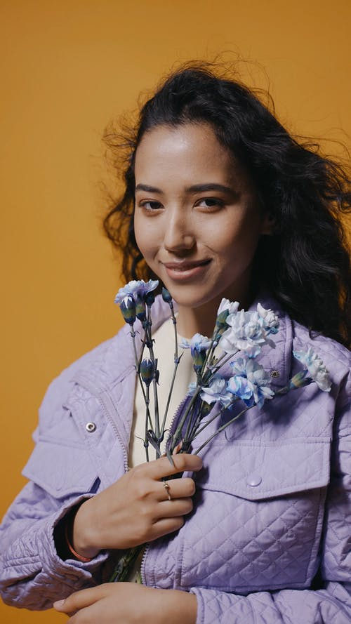 A Woman Posing and Smiling While Holding Flowers