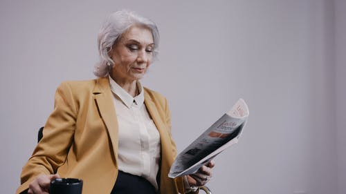 Woman Drinking Coffee While Reading a Newspaper