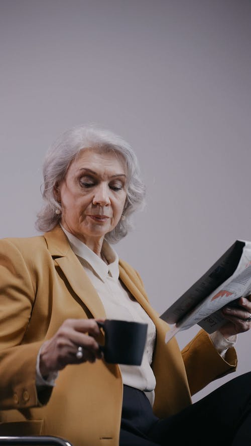 Woman Drinking in a Cup while Reading