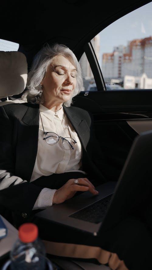 Woman Using a Laptop Inside a Car