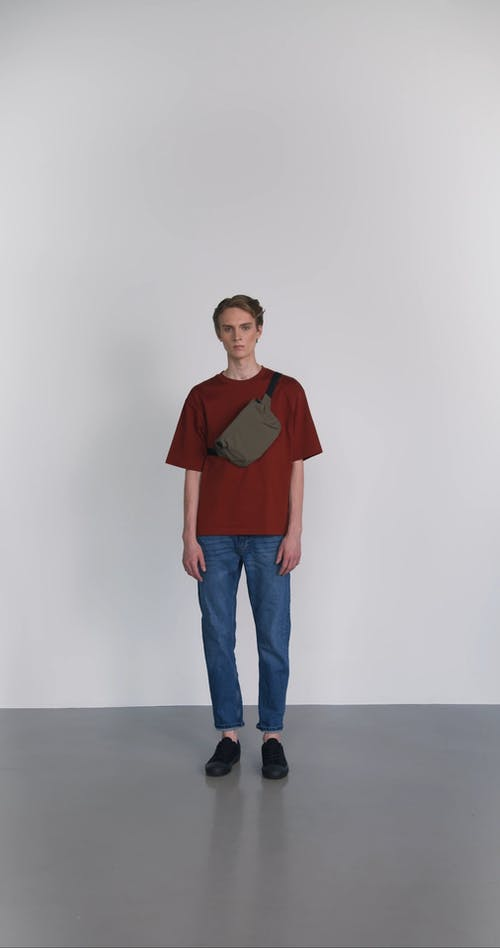 A Man Removing His Bag and Wearing Another Bag While Looking at the Camera