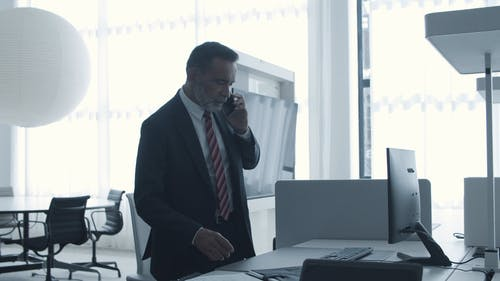 Man Talking On The Phone While Using a Computer