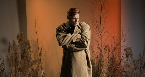 A Man Covering Himself with a Brown Trench Coat