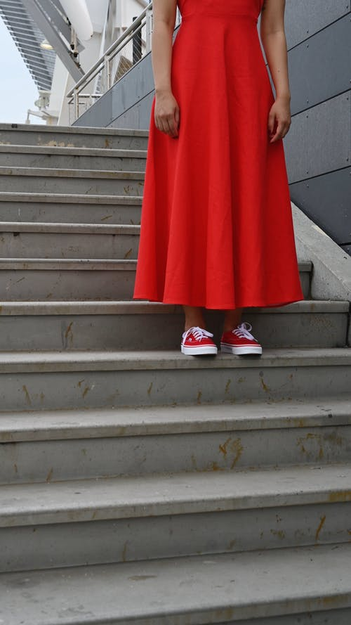 A Woman in an Orange Dress Standing on a Flight of Stairs