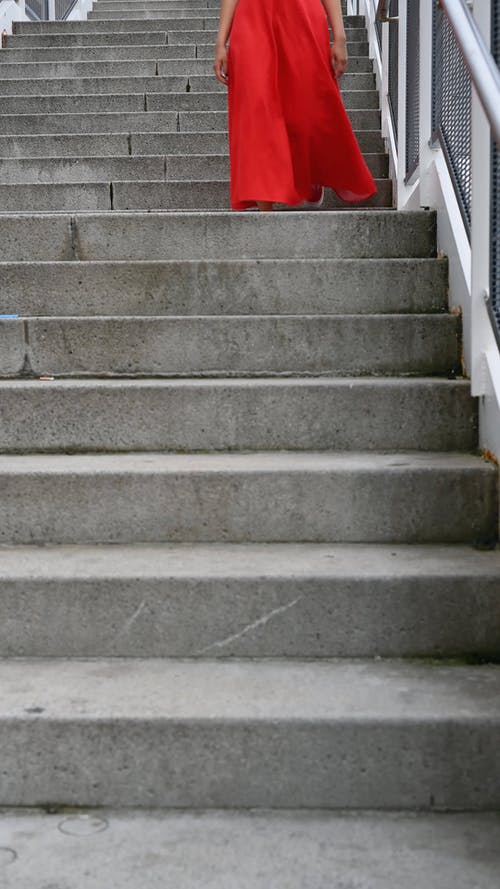A Person Walking Down the Concrete Stairs