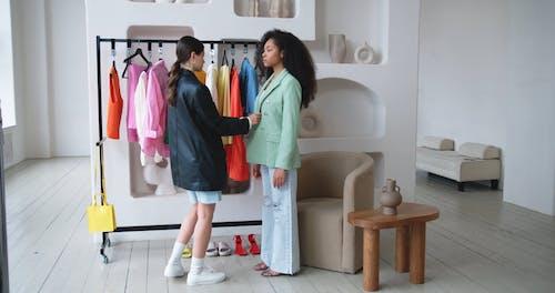 A Fashion Designer Dressing A Model