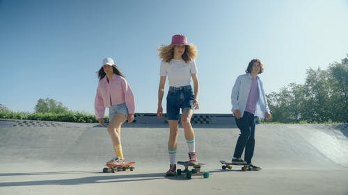 Two Young Women and Man Riding On Skateboards