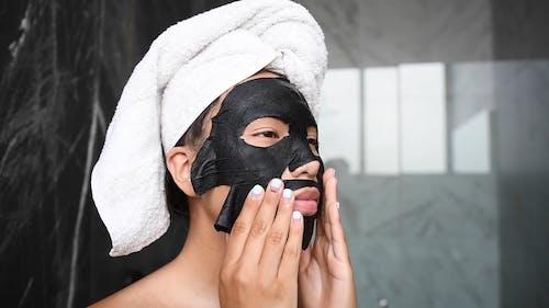 Woman Putting On Facial Mask