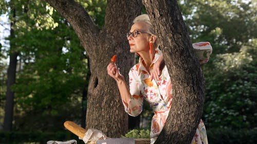 A Woman Eating a Strawberry by a Tree