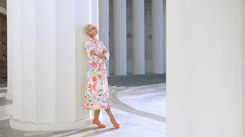 An Elderly Woman Posing on a Column