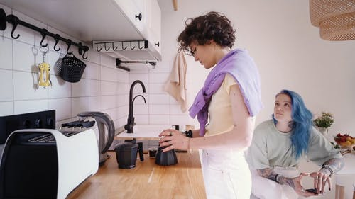 A Woman Looking at Her Partner while Fixing the Coffee Maker
