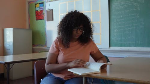 A Young Woman Reading a Book in a Classroom