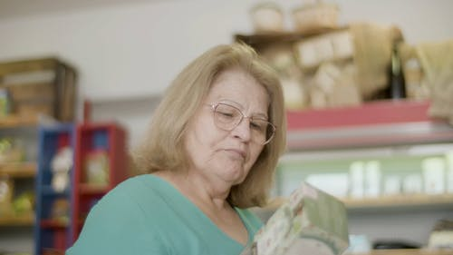 An Elderly Woman Looking at an Item in a Shop