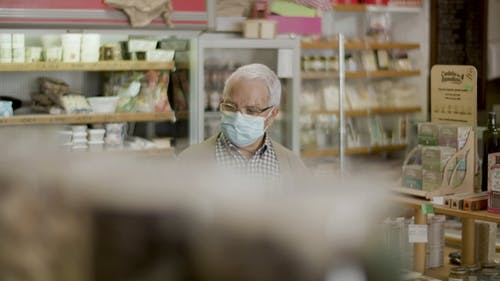 An Elderly Man Looking at an Item in a Store
