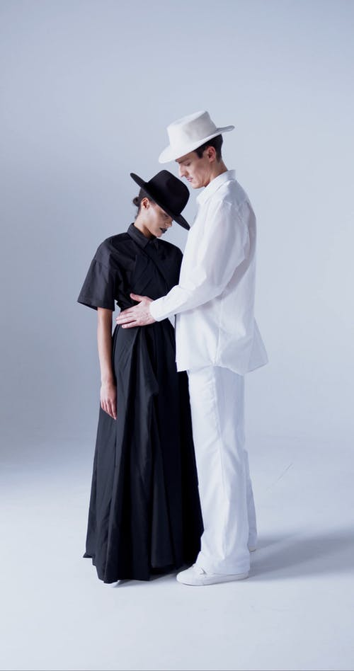 A Man in White Suit and a Woman Wearing a Black Dress