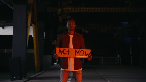 A Man Holding a Cardboard Sign