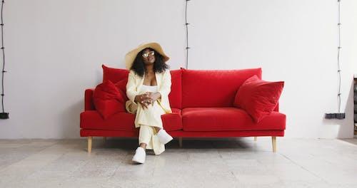 Woman Wearing A Beach Hat Sitting On a Sofa
