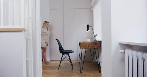 A Woman Sitting on a Scandinavian Chair