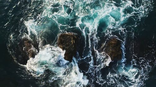 Aerial View of a Waves Crashing on Rocks