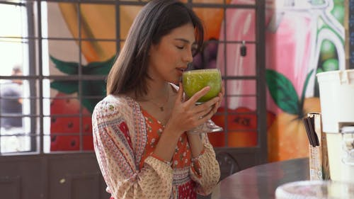 A Woman Drinking a Fruit Juice