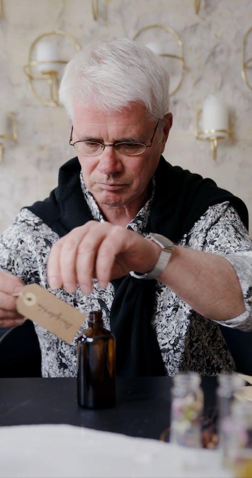 An Elderly Man Placing a Label on Brown Bottle