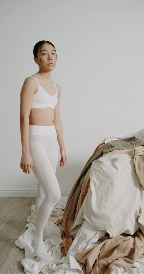 Woman in Underwear Posing by a Pile of Clothes